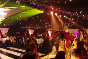 Black and white theme party inside marquee with dancefloor, visual lightning, golden chiavari chairs and curtain backdrops for rental