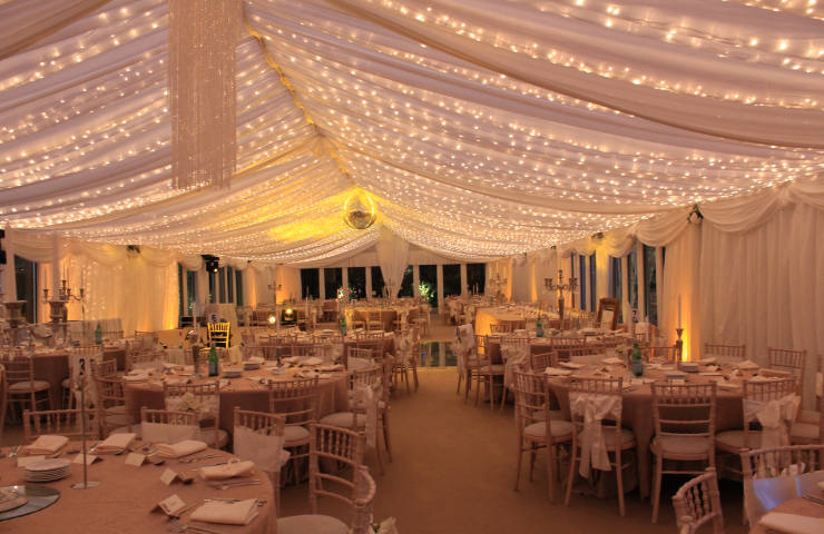 Wedding Interior with white marquee roof a disco ball and fairy lights