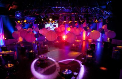 corporate ceiling decor with paper lanterns, hanging bands of drapes and pin spotted tables