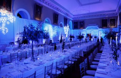 corporate christmas dinner at the RHK in Dublin with long trestle tables, golden candelabras, christmas green centre pieces, white drapery and soft blue lightning with snow flakes projectors