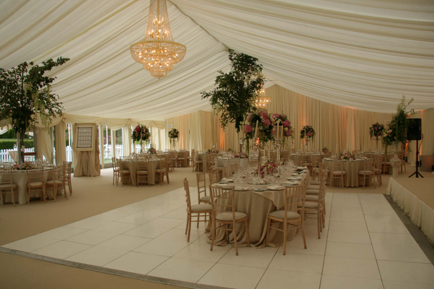 elegant wedding event draping for a marquee styling with golden chandelier, ivory drape ceiling and walls, white chiavary chairs and high floral center pieces