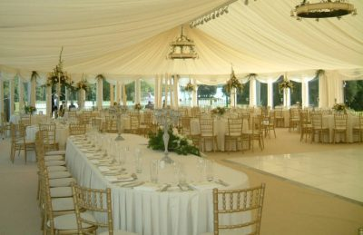 ivory wedding marquee drapery design with chandeliers and golden chiavary chairs