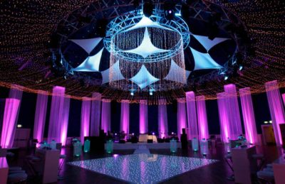 party decor with fairy light ceiling, sparkly white dance floor and square fringe tubes hanging lit in pink