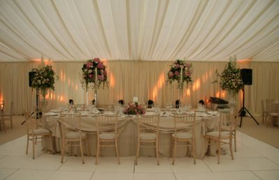 wedding top trestle table with hessian linen, floral arragements and white drapery on walls and ceiling