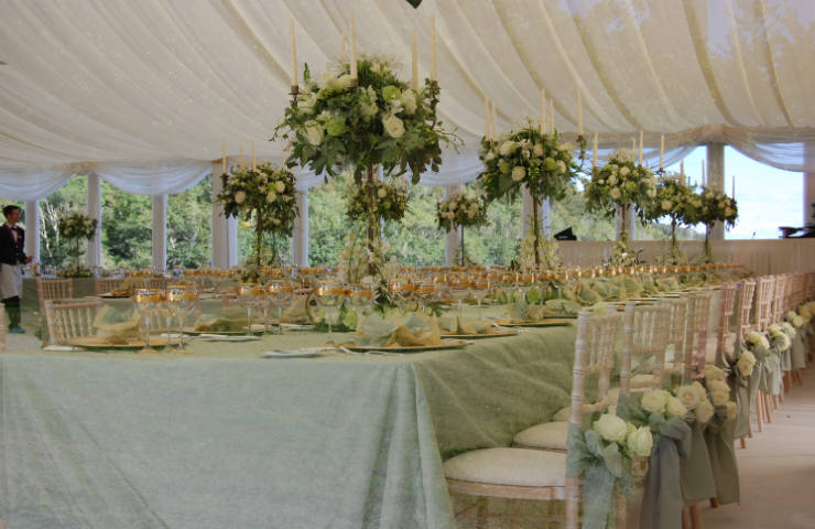 Marquee wedding interiors trestle table decorated with candles and flowers in white and turquose