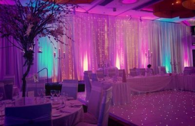 Wedding hotel interiors design with lit up backdrop and wedding top table