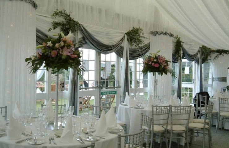 wedding marquee design with white and silver drapes and high red roses center pieces