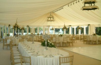 wedding marquees interior design with golden chiavary chairs, glass candelabras and white drapery