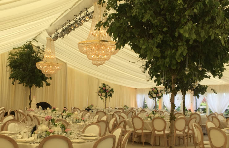 wedding marquees interiors with ivory drapes and high tree center pieces and chandeliers