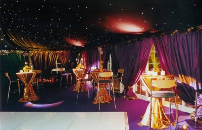 50th Private Party Decor with purple drapery, golden high pod table linen and a star like marquee ceiling