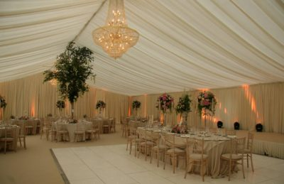 elegant wedding marquee decor with golden chandelier, ivory drape ceiling and walls, white chiavary chairs and high floral center pieces