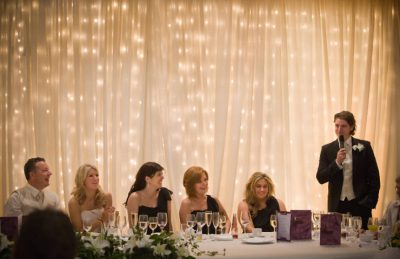 wedding backdrop drapery rental and installation in ivory and white with twinkle lights