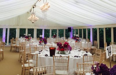 Marquee wedding interiors with white drapes, chiavary chairs and orchid center pieces