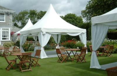snow white pagodas for hire for wedding decor outdoors in a garden with wooden chairs and table